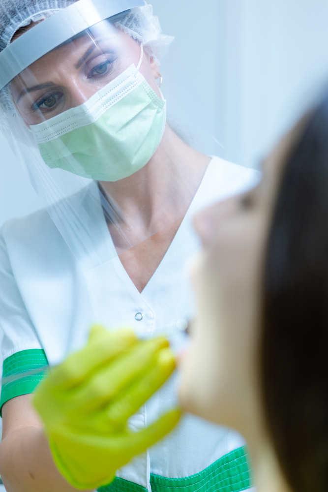 Beautiful,Female,Dentist,With,Face,Mask,And,Visor,As,Coronavirus