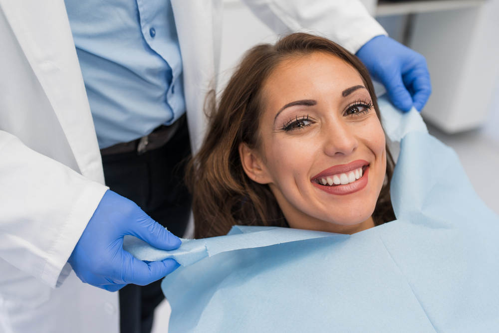 Doctor,Fixing,Female,Patient,Napkin,In,Modern,Dental,Clinic