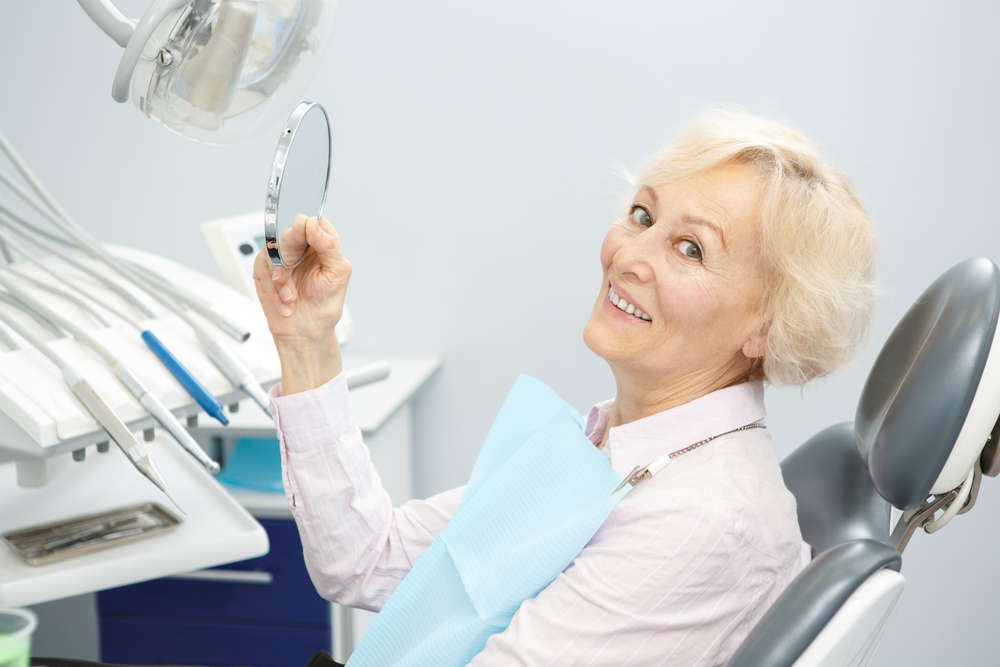 Senior,Female,Patient,Smiling,To,The,Camera,Holding,A,Mirror