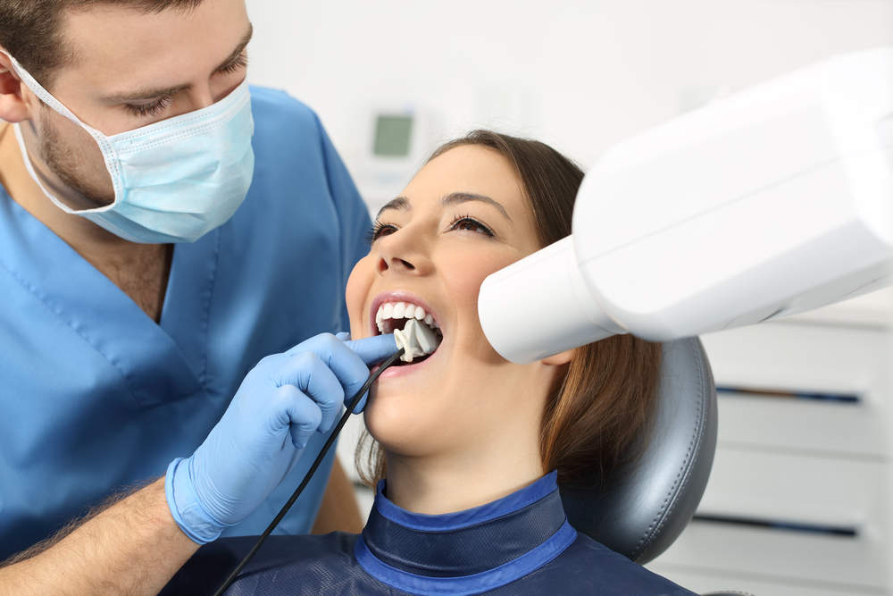 Dentist,Taking,A,Teeth,Radiography,To,A,Patient,In,An