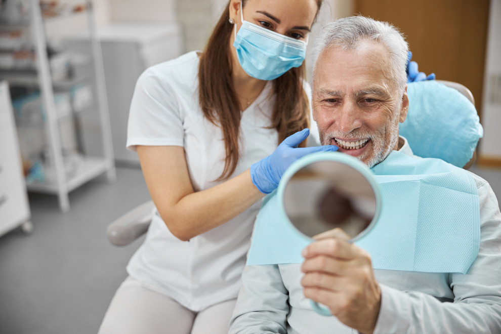 Elderly,Man,And,His,Young,Female,Dentist,Smiling,While,Looking