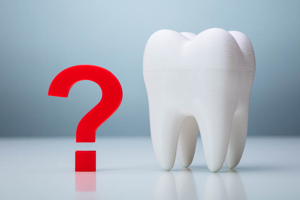 Question,Mark,Near,White,Tooth,Over,Gray,Background