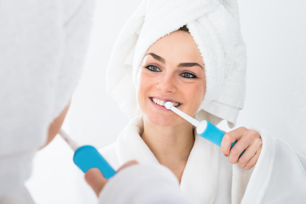 Close-up,Of,A,Woman,In,Bathrobe,Brushing,Teeth