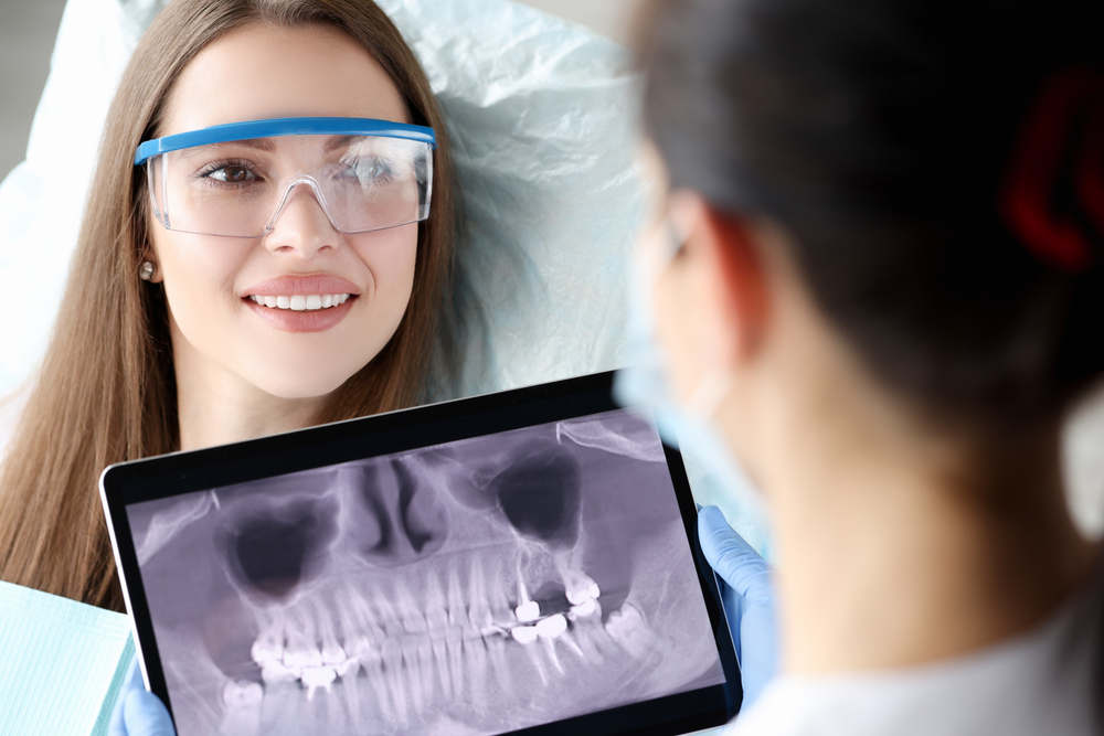 Dentist,Holding,Digital,Tablet,With,3d,Picture,Of,Teeth,In